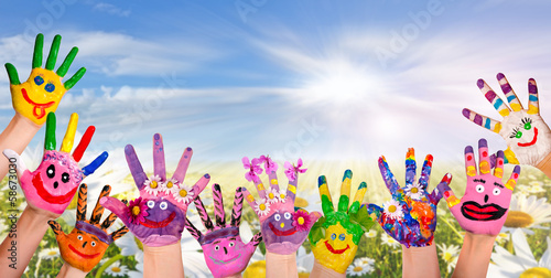Hände spielender Kinder vor Blumenwiese - 58673030