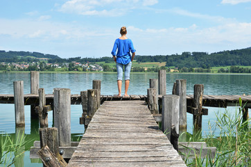 Girl on the wooden jetty. Switzerland