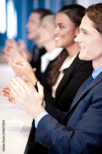 Team of four corporates applauding
