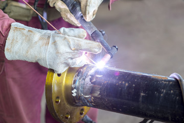 Hands welding a metal pipe