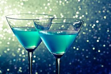 two glasses of blue cocktail on dark green tint light bokeh