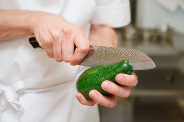 Chef is cutting avocado with knife