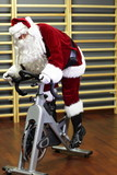 Santa Claus training on exercise bike at the gym
