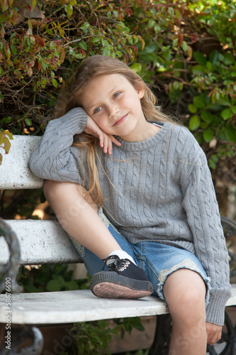 happy little girl sitting on the bench