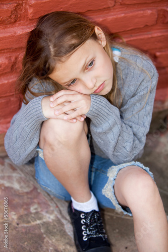 sad little girl sitting against the wall