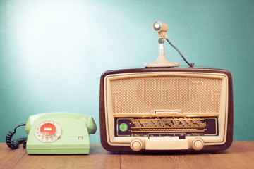 Retro radio with green light, microphone and telephone on table