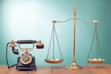 Law scales and vintage rotary telephone on table
