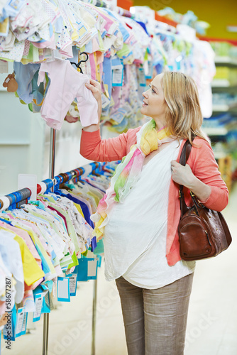 Young pregnant woman at clothes shop
