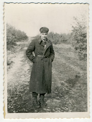 CIRCA 1955: Photo of the young soldier in a long coat