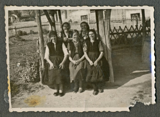 CIRCA 1950: Five young women sitting on an old wooden bench