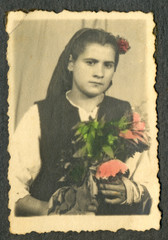 CIRCA 1940 - Woman with flowers in her arms (hand colored)