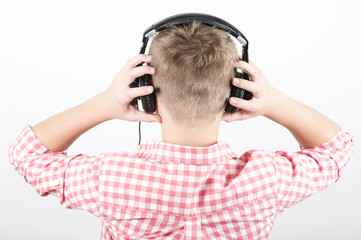 Teenager listens music with headphones, rear view