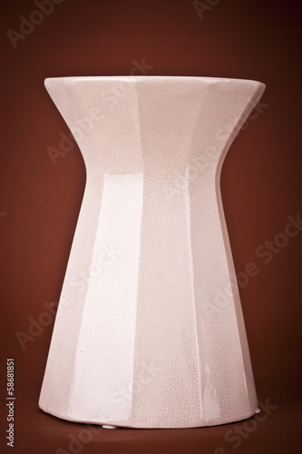 Modern clay vase on brown background