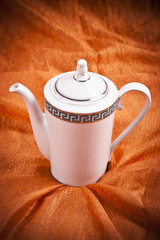 teapot isolated on orange fabric  background