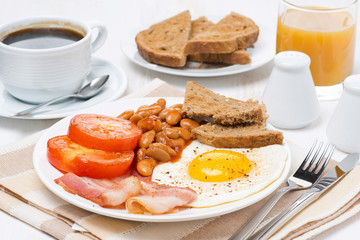 Traditional English breakfast with fried eggs, bacon and beans