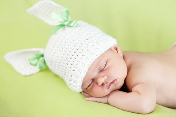 Funny sleeping newborn baby. Girl weared in bunny hat.