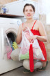 Young woman in red using bag for laundry