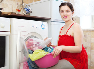 housewife  in red  loading the washing machine