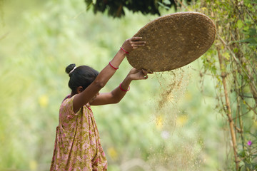Nepali woman whisking rice in Terai