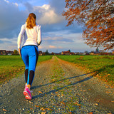 Sporty female walking and running on autumn road