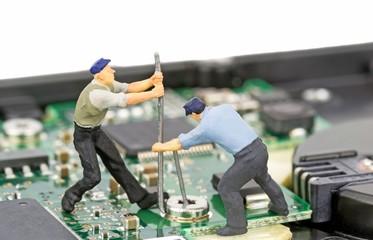 Miniature engineers repairing a computer hard drive