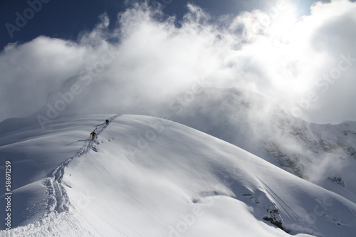Skiers climbing a snowy mountain