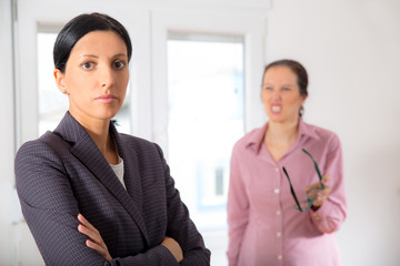 Business woman yelling at another business woman