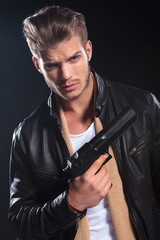 hitman in leather clothes holding a big gun in his hand