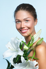 Beautiful young woman with with white lily flowers, female face