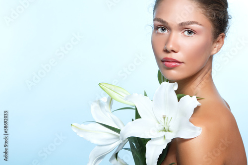 Beautiful young woman with with lily flowers, female face and sh