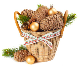 Basket with Christmas ornaments and cedar cones, isolated