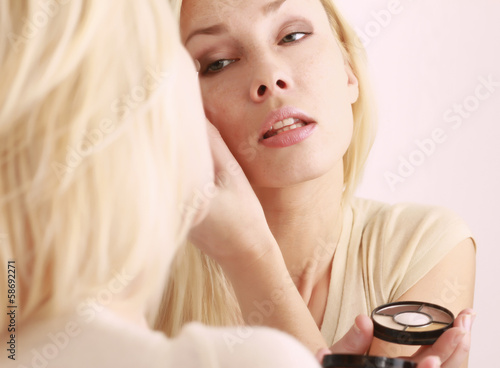 Woman caring of her skin on the face standing near mirror