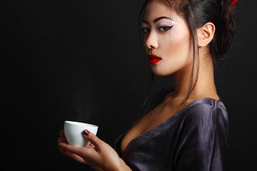 Young beautiful asian woman and tea ceremony, copyspace over bla