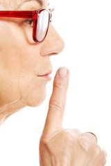 Elderly woman is having finger on her lips. Profile.