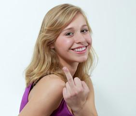 Jugendliche zeigt lachend den Mittelfinger