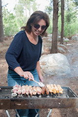 woman cooking meat on portable barbecue