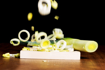 Green, fresh leek and its slices falling down.