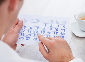 Man Marking With Pen And Looking At Date On Calendar