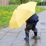 Child with umbrella in puddle
