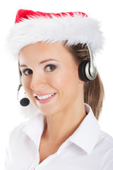 Young business woman with headphose, microphone in santa hat.