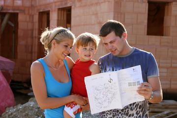 Familie vor Rohbau baut ein Haus