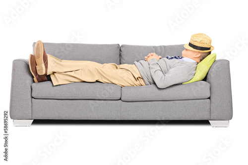 Mature man with hat over his head sleeping on a sofa