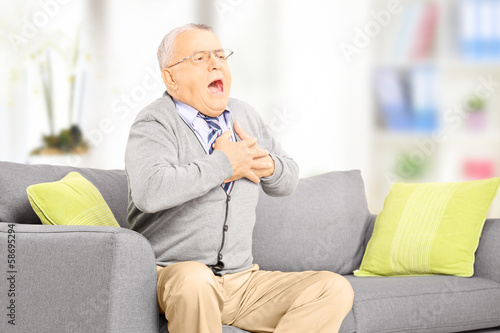 Senior man seated on sofa having a heart attack at home