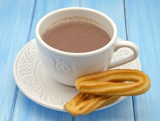 Taza con chocolate caliente y churros