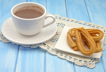 Taza con chocolate caliente y churros