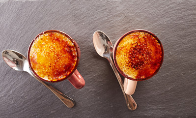 Two cups of creme brulee on a slate board
