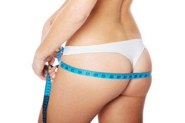 Female's buttocks with measuring tape.