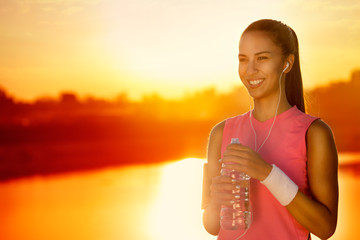 Smiling sporty woman with bottle of water