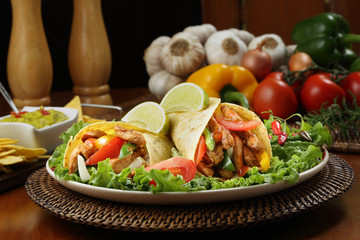 chicken fajita  with guacamole and tortillas - dish of mexico