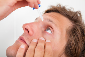 Young Man Putting Eye Drops